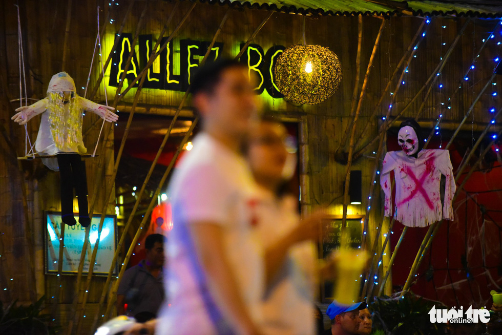 Ghost figures are hung in front of drinking places in Pham Ngu Lao Street, District 1, Ho Chi Minh City. Photo: Tuoi Tre