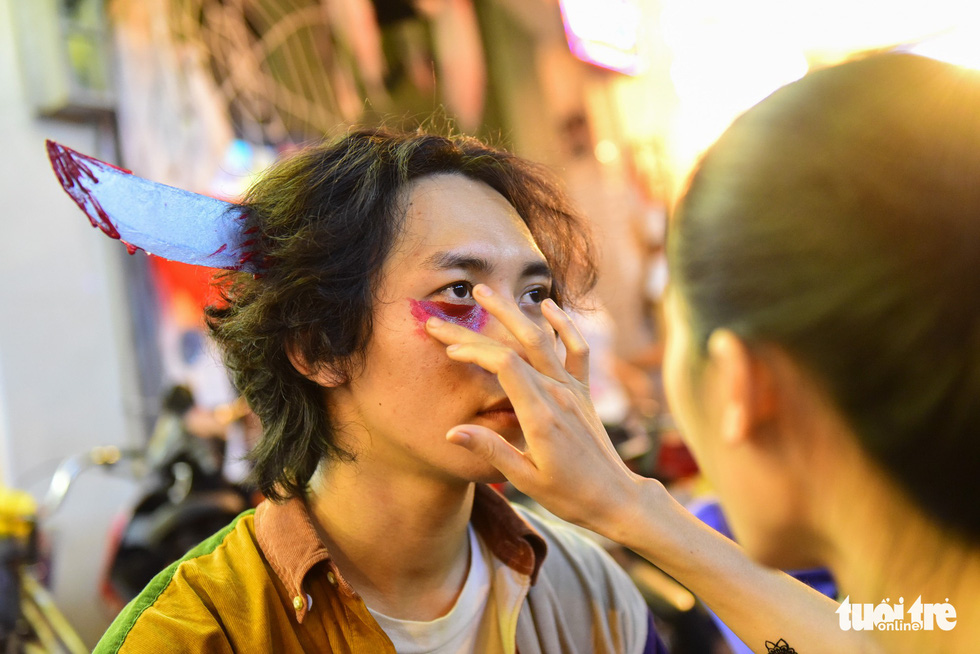 A man has his face made up in Halloween theme. Photo: Tuoi Tre