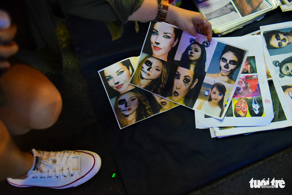 Catalogs of Halloween make-ups are printed for customers' selection. Photo: Tuoi Tre