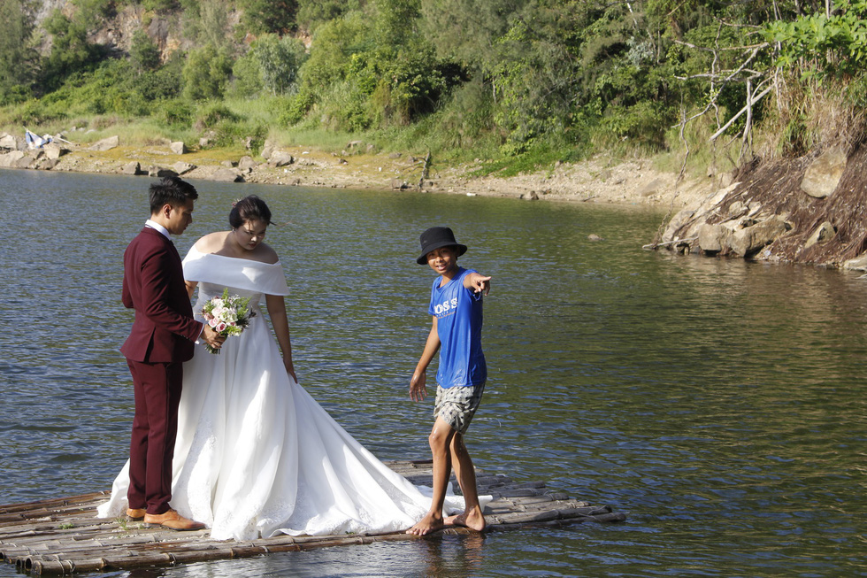 Tai, a teen boy who controls bamboo rafts to carry couples for photo shoots at the Green Lake in Da Nang, shows a couple how to pose for their wedding photo. Photo: Tuoi Tre
