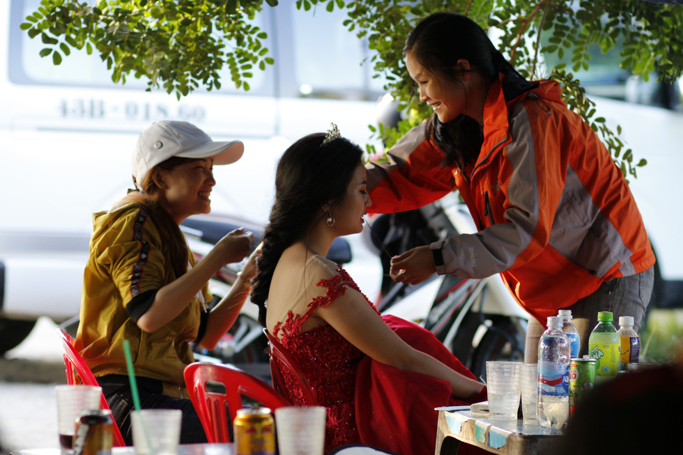 A bride has her make-up done at a street drink stall near a photo spot. Photo: Tuoi Tre