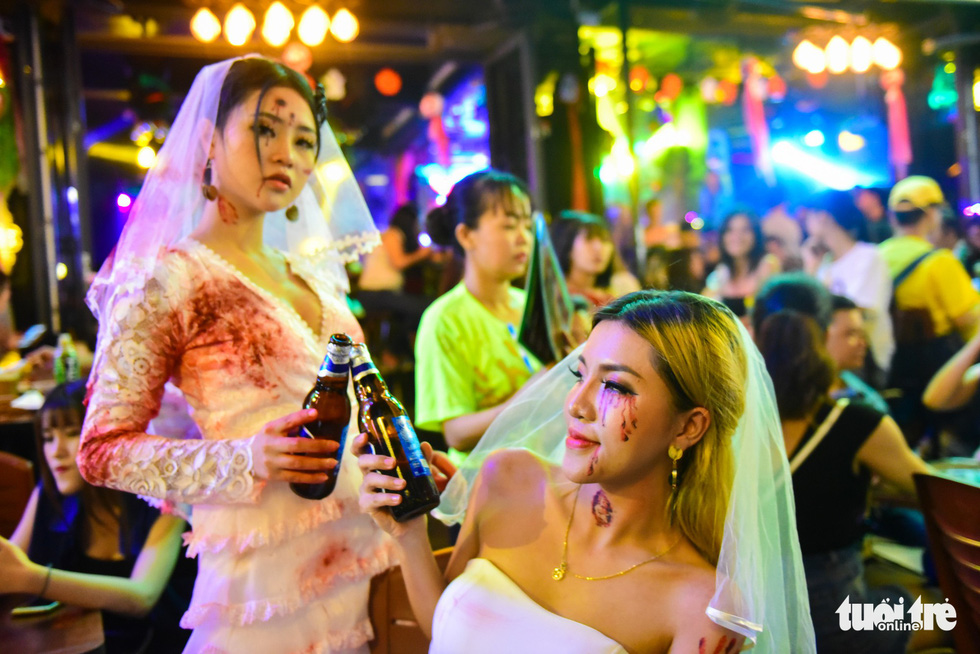 Two Vietnamese women masquerading as ghost brides make a toast. Photo: Tuoi Tre