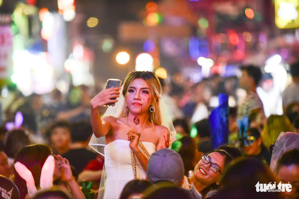 A Vietnamese woman takes a scary selfie on Bui Vien Street on October 31, 2018. Photo: Tuoi Tre