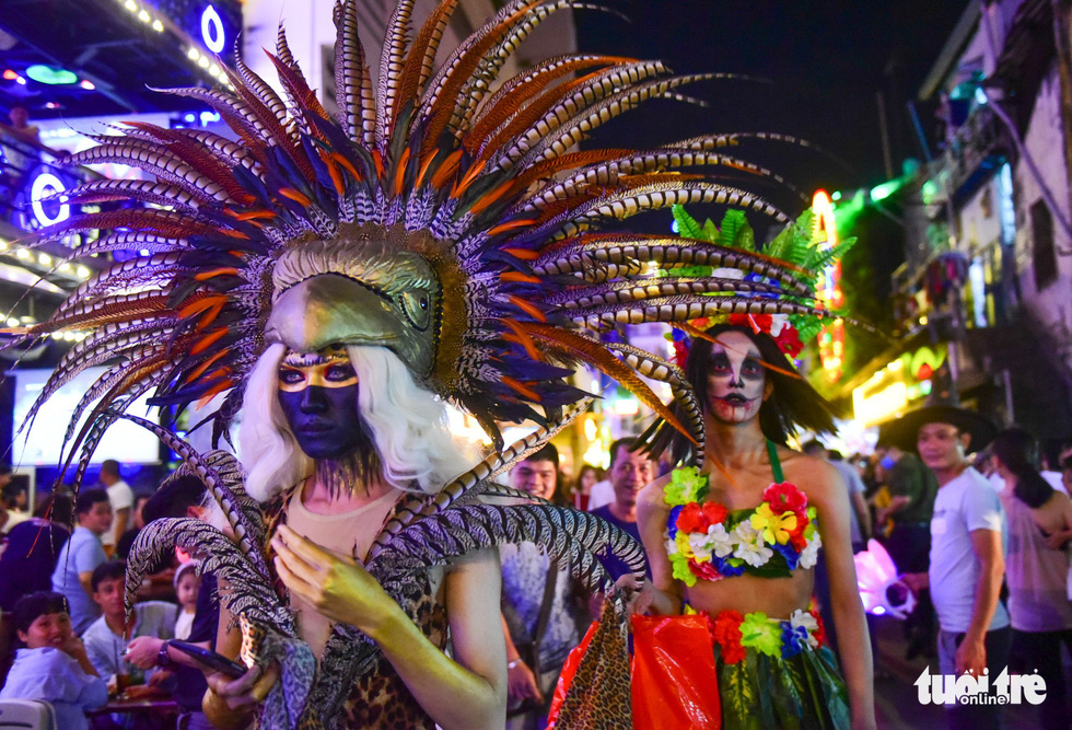 Two costumed revelers display colorful and traditional costumes, like those at carnivals, on Bui Vien Street on October 31, 2018. Photo: Tuoi Tre