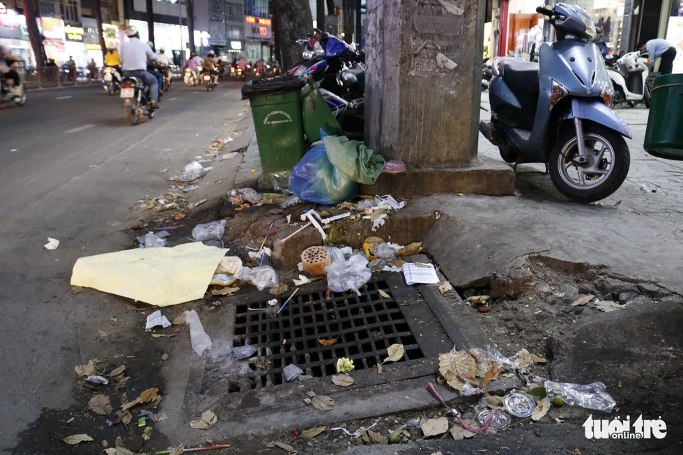 Rubbish is littered at a manhole cover despite the presence of a recycle bin.