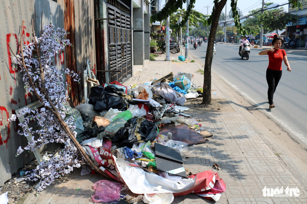 Pedestrians are unable to walk on the sidewalk as it is blocked by a malrge amount of garbage.