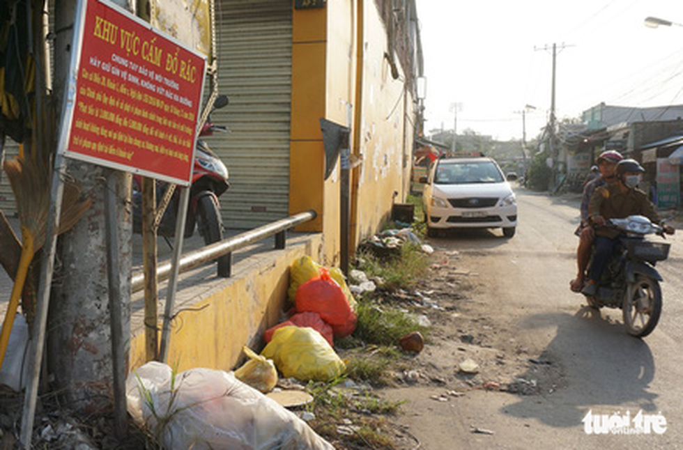 Rubbish is often dumped at night despite a prohibition sign at a neighborhood in Binh Chanh District.