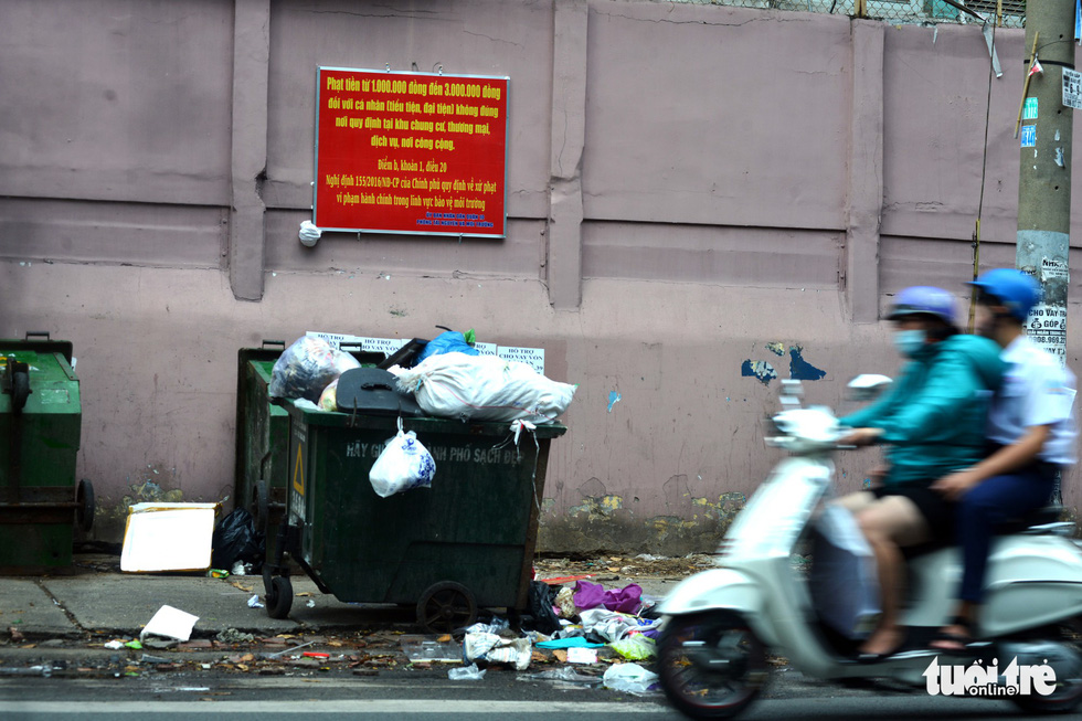 Garbage containers are overfilled along a street.