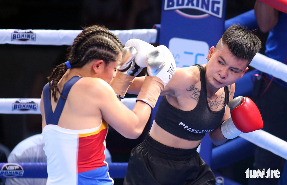 Nguyen Thi Thu Nhi (R) delivers a blow to Gretchen Abaniel in their showdown at the Victory8 boxing tournament in Ho Chi Minh City on October 3, 2018. Photo: Tuoi Tre