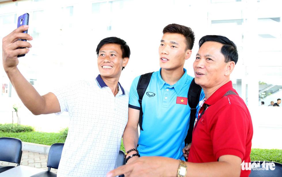 Fans take photo with Vietnamese goalkeeper Bui Tien Dung upon his team's arrival at the Wattay International Airport in Laos on November 5, 2018. Photo: Tuoi Tre