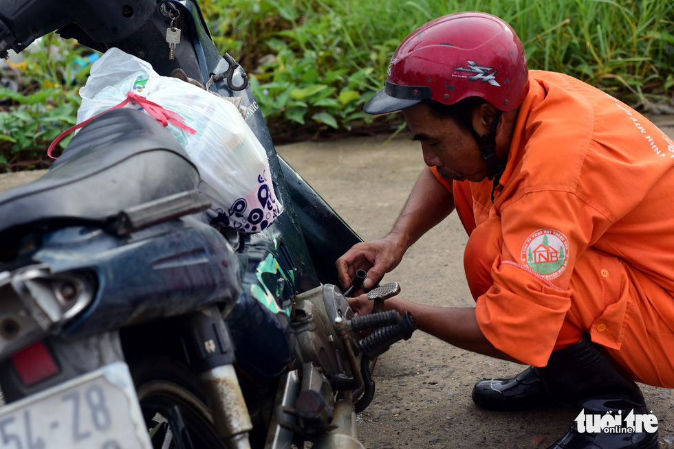 A man fixes his motorbike after it breaks down due to the floodwater.