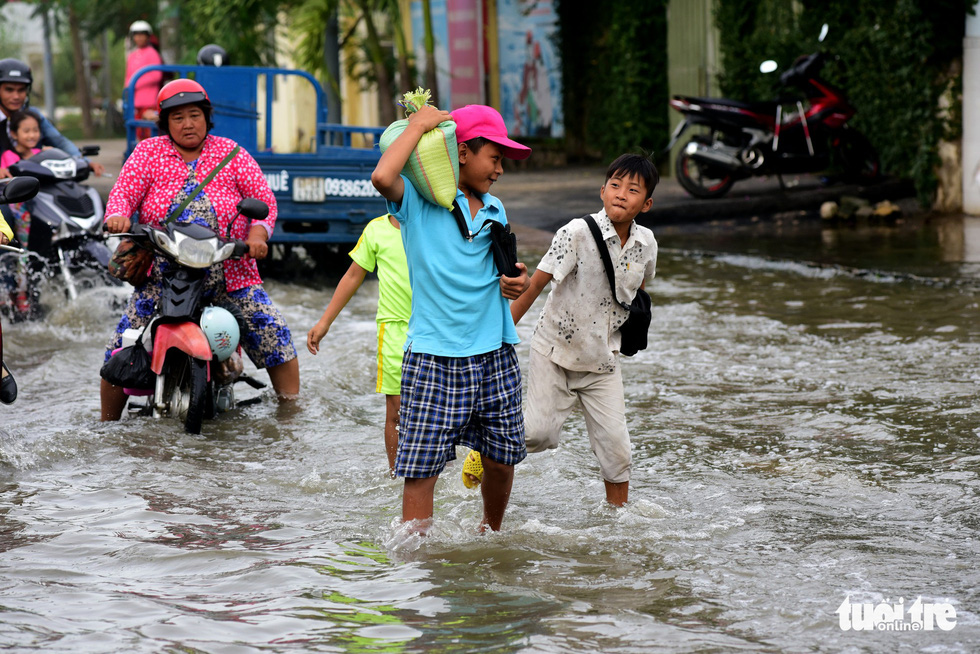 Children walk on an inundated street.