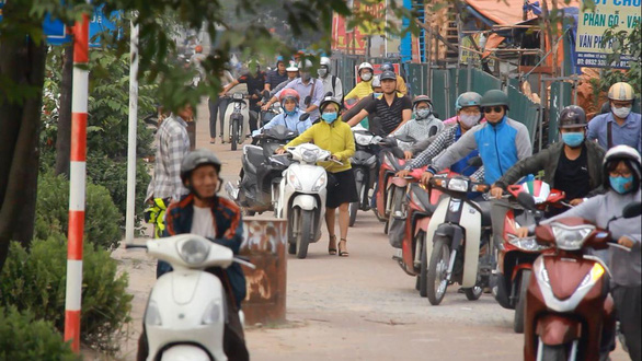 In Hanoi, commuters push motorbikes wrong way on sidewalk to avoid congestion