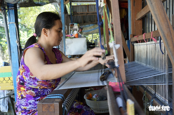 A woman works by her loom in the Long Khanh weaving village in Dong Thap Province, southern Vietnam. Photo: Tuoi Tre
