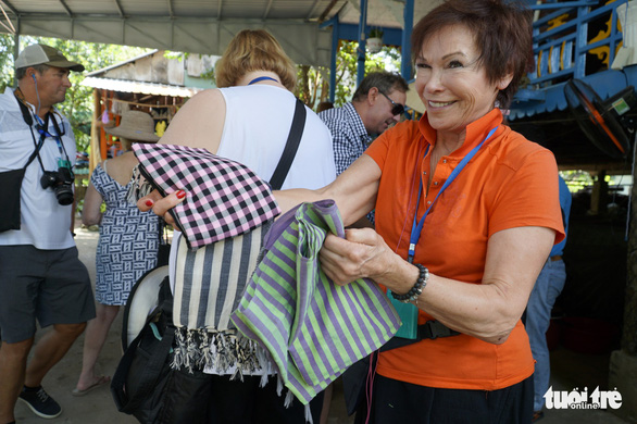 A visitor shows checkered and striped shawls in the Long Khanh weaving village in Dong Thap Province, southern Vietnam. Photo: Tuoi Tre