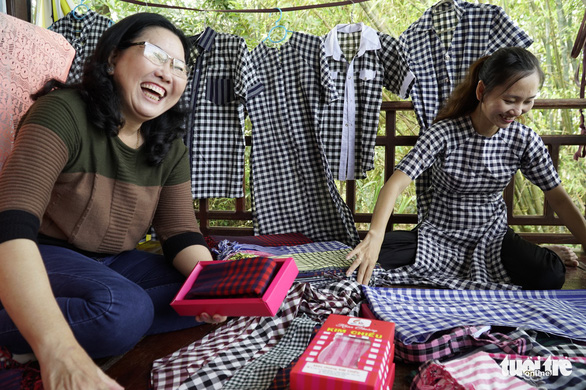 A tourist sits with a seller at a shop in the Long Khanh weaving village in Dong Thap Province, southern Vietnam. Photo: Tuoi Tre