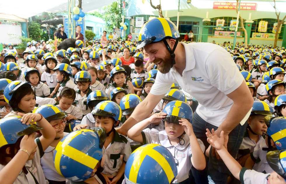 Johan Alvin, second secretary of Embassy of Sweden, shows students how to wear a helmet properly. Photo: Tuoi Tre