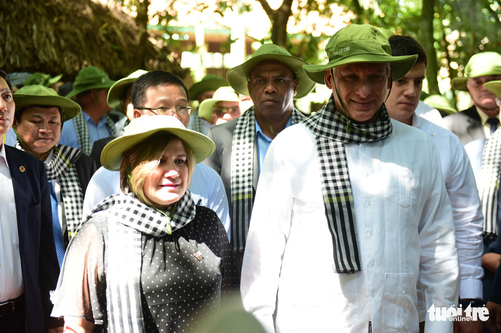 The president and his spouse wear traditional hats and scarves during their visit.