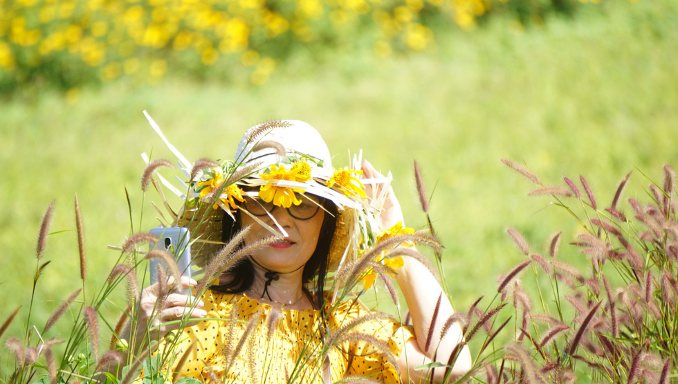 A woman takes a selfie with the flowers.