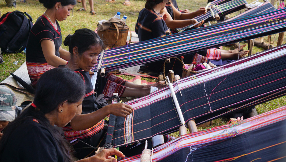 Local villagers weave brocade at the event.