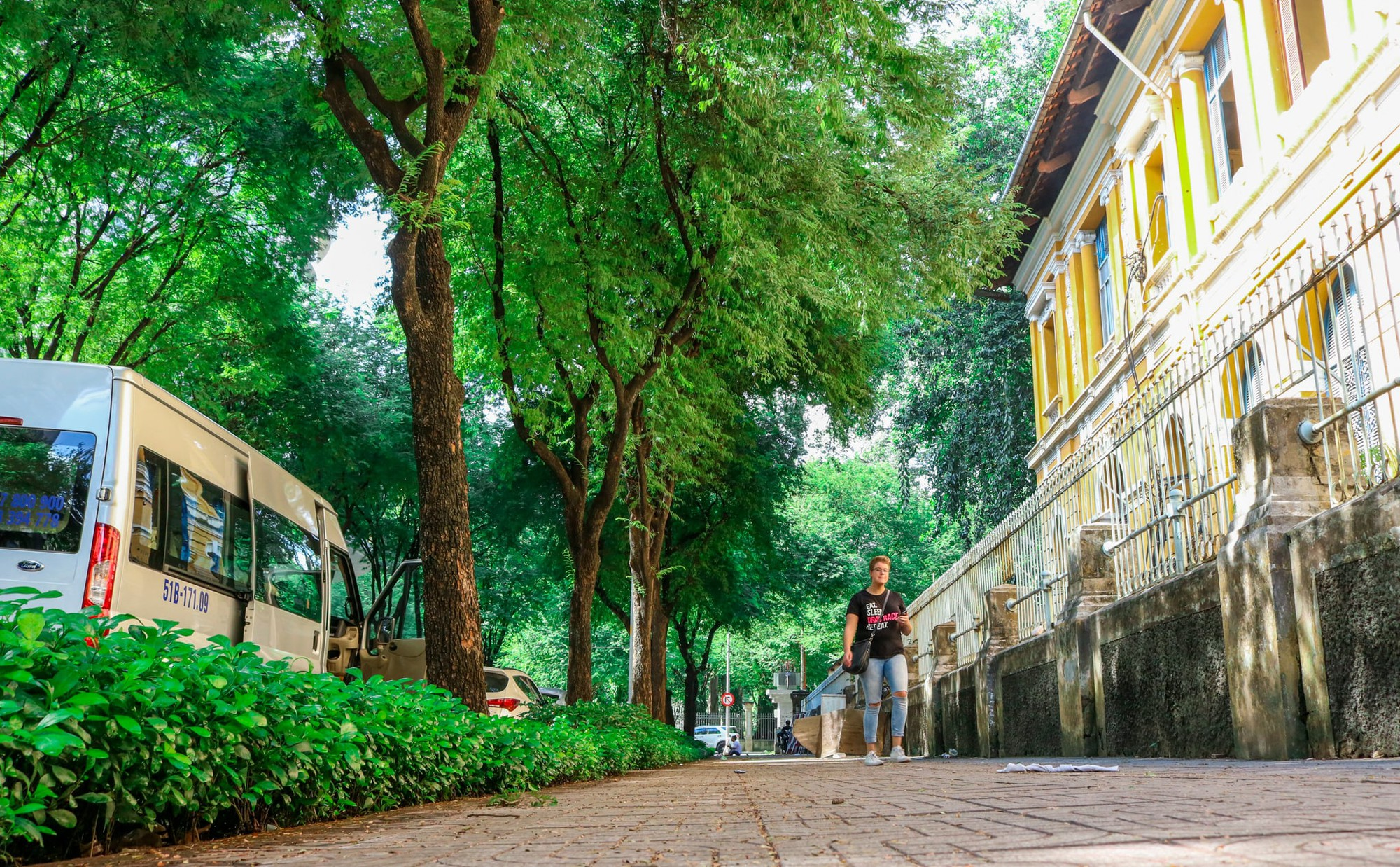 A foreigner walks under tamarinds on a street in Ho Chi Minh City, Vietnam. Photo: Tuoi Tre