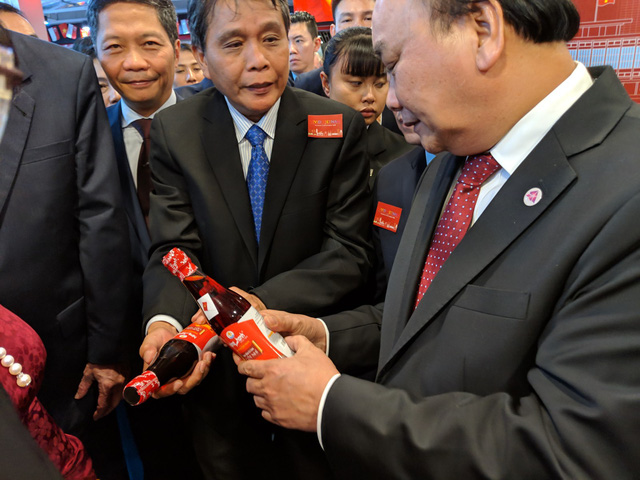PM Phuc reviews a bottle of fish sauce made in Vietnam. Photo: Tuoi Tre