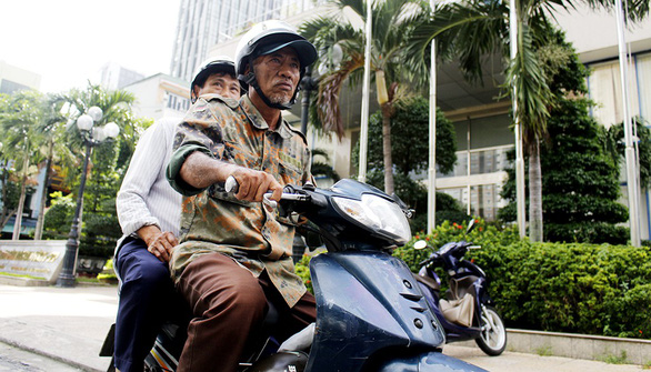 Nguyen Rem carries a passenger on his motorcycle in Da Nang City, central Vietnam. Photo: Tuoi Tre