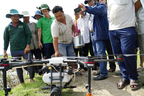 Men surround an agricultural drone near a paddy field in Dong Thap Province, southwestern Vietnam November 14, 2018. Photo: Tuoi Tre