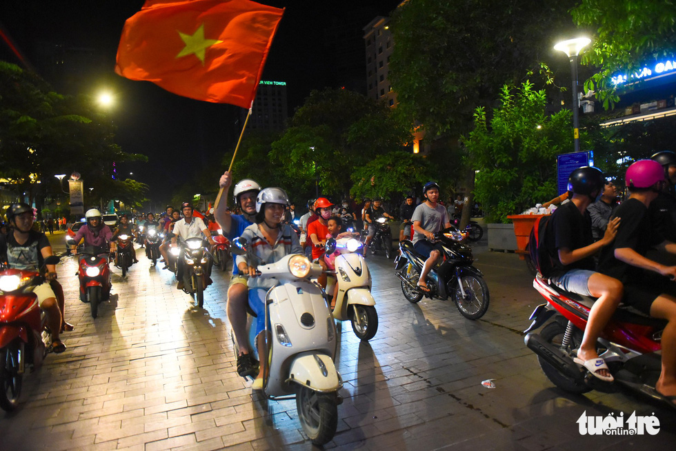 A foreign man and a Vietnamese woman join the crowd of people on motorbikes touring around the Nguyen Hue pedestrian area on November 16, 2018. Photo: Tuoi Tre