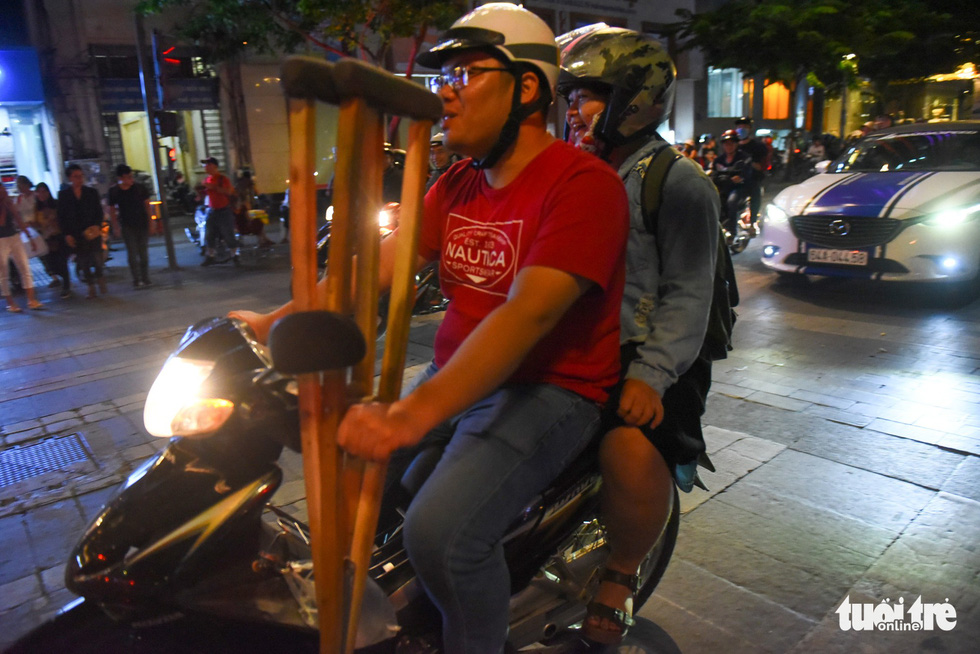 A couple carrying a pair of crutches joins the crowd of people on motorbikes touring around the Nguyen Hue pedestrian area on November 16, 2018. Photo: Tuoi Tre