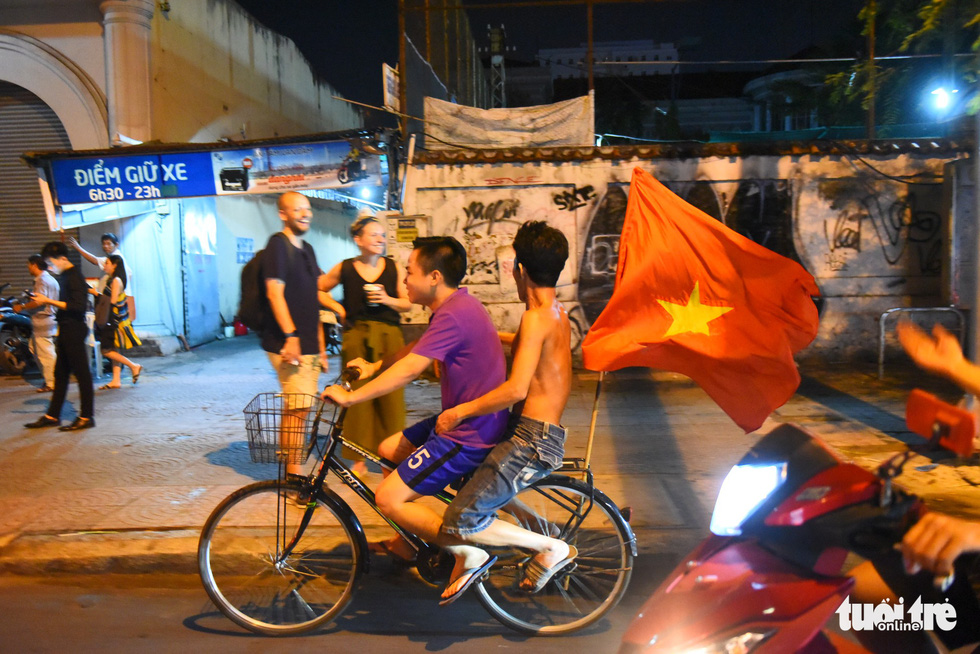 Two young men ride a bicycle that carries a Vietnam national flag at the end to celebrate Vietnam's 2-0 victory against Malaysia at the 2018 AFF Championship on November 16, 2018. Photo: Tuoi Tre