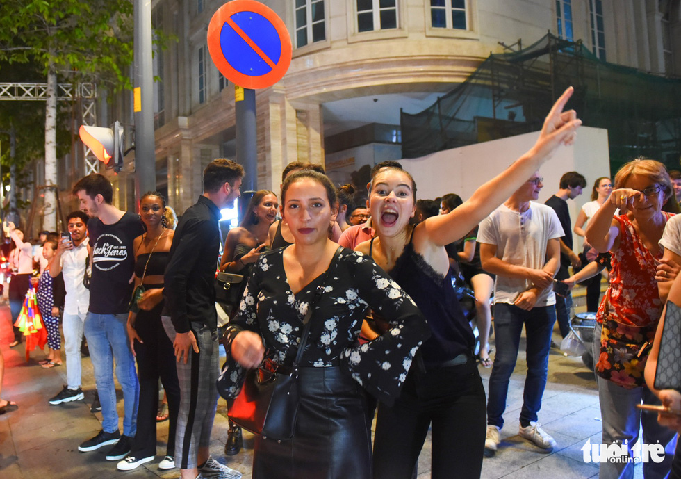 Two foreign women join the crowd of people to celebrate Vietnam's 2-0 victory against Malaysia at the 2018 AFF Championship on November 16, 2018. Photo: Tuoi Tre