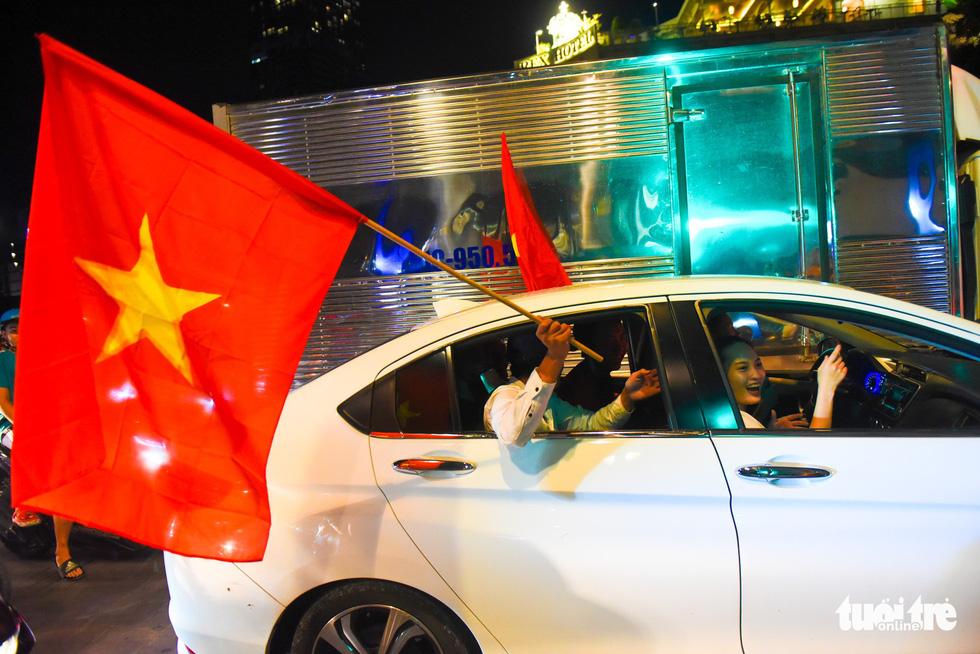 A man in a car carries a Vietnam national flag to celebrate Vietnam's 2-0 victory against Malaysia at the 2018 AFF Championship on November 16, 2018. Photo: Tuoi Tre