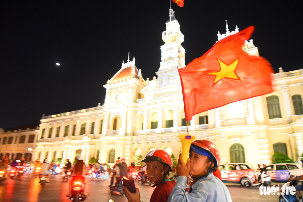 Two men join the crowd of people on motorbikes touring around the Nguyen Hue pedestrian area on November 16, 2018. Photo: Tuoi Tre