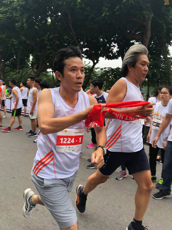 Members of a team from Tuoi Tre (Youth) newspaper pass the ribbon called Tasuki.