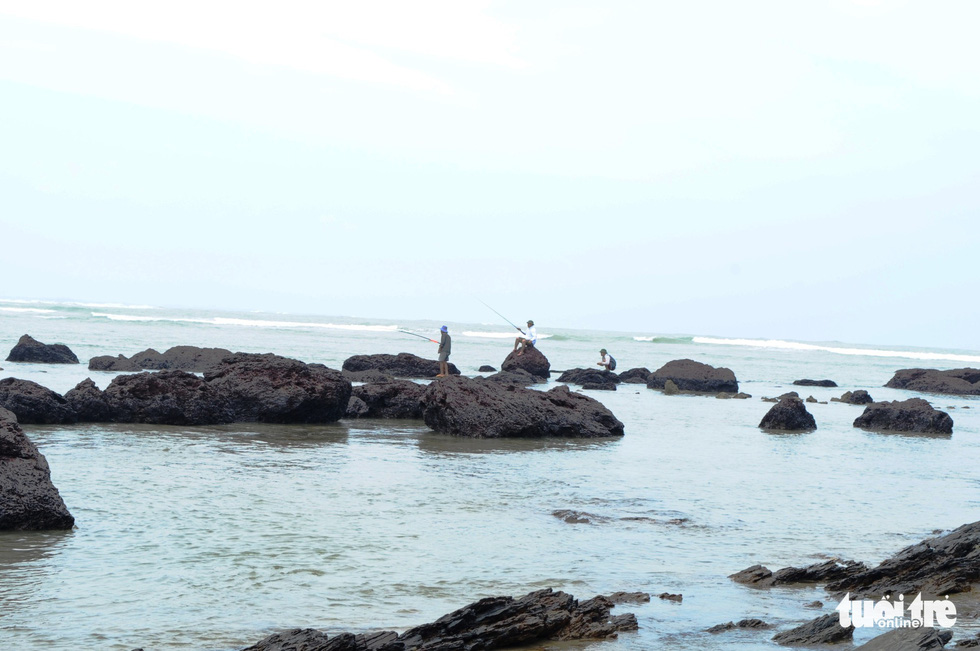 People fish near the rocks on Tam Hai Island.