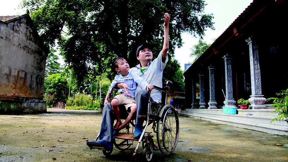 Phung Van Truong sits in a wheelchair with his son in a village in suburban Hanoi, Vietnam. Photo: Tuoi Tre