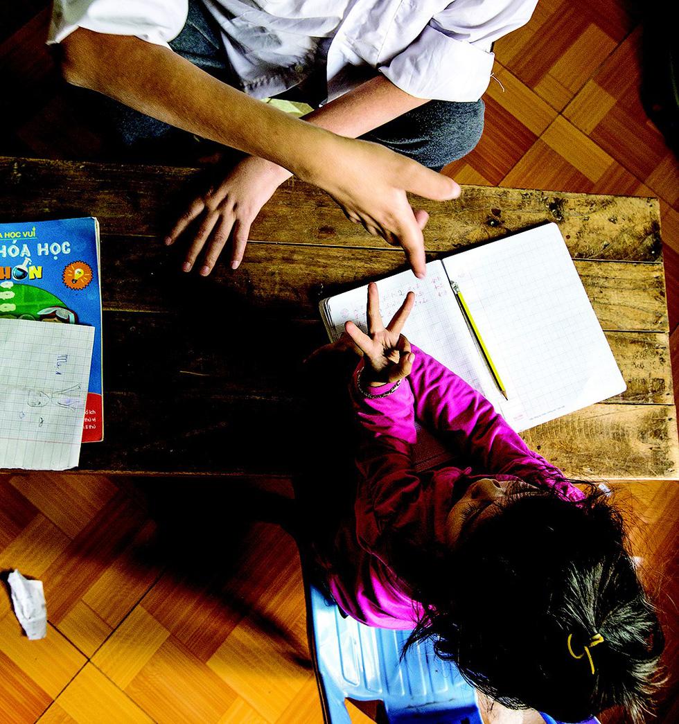 Phung Van Truong teaches a girl math at his house in suburban Hanoi, Vietnam. Photo: Tuoi Tre