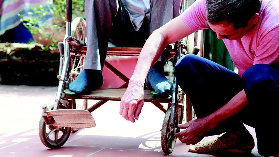 A man fixes Phung Van Truong's wheelchair in a village in suburban Hanoi, Vietnam. Photo: Tuoi Tre