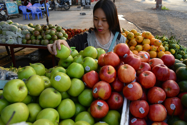 A customer chooses foreign-made apples at a store on a street in Ho Chi Minh City. Photo: Tuoi Tre