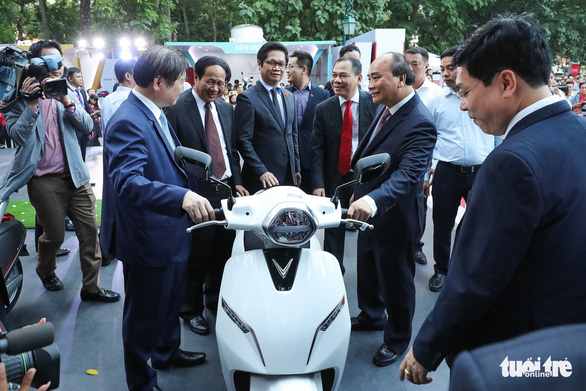 Prime Minister Nguyen Xuan Phuc and other delegates watch a VinFast motorcycle. Photo: Tuoi Tre