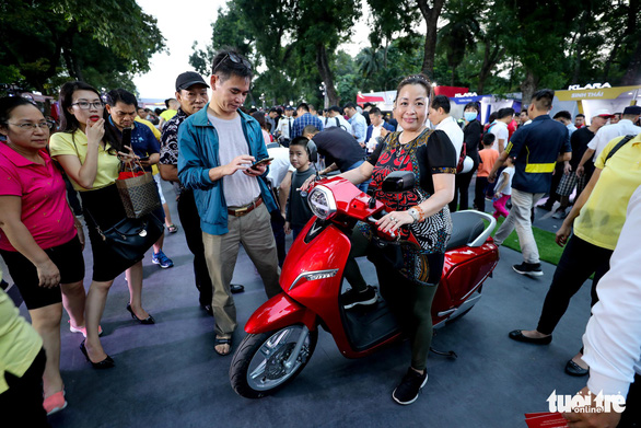 A visitor tries riding a VinFast electric motorcycle. Photo: Tuoi Tre