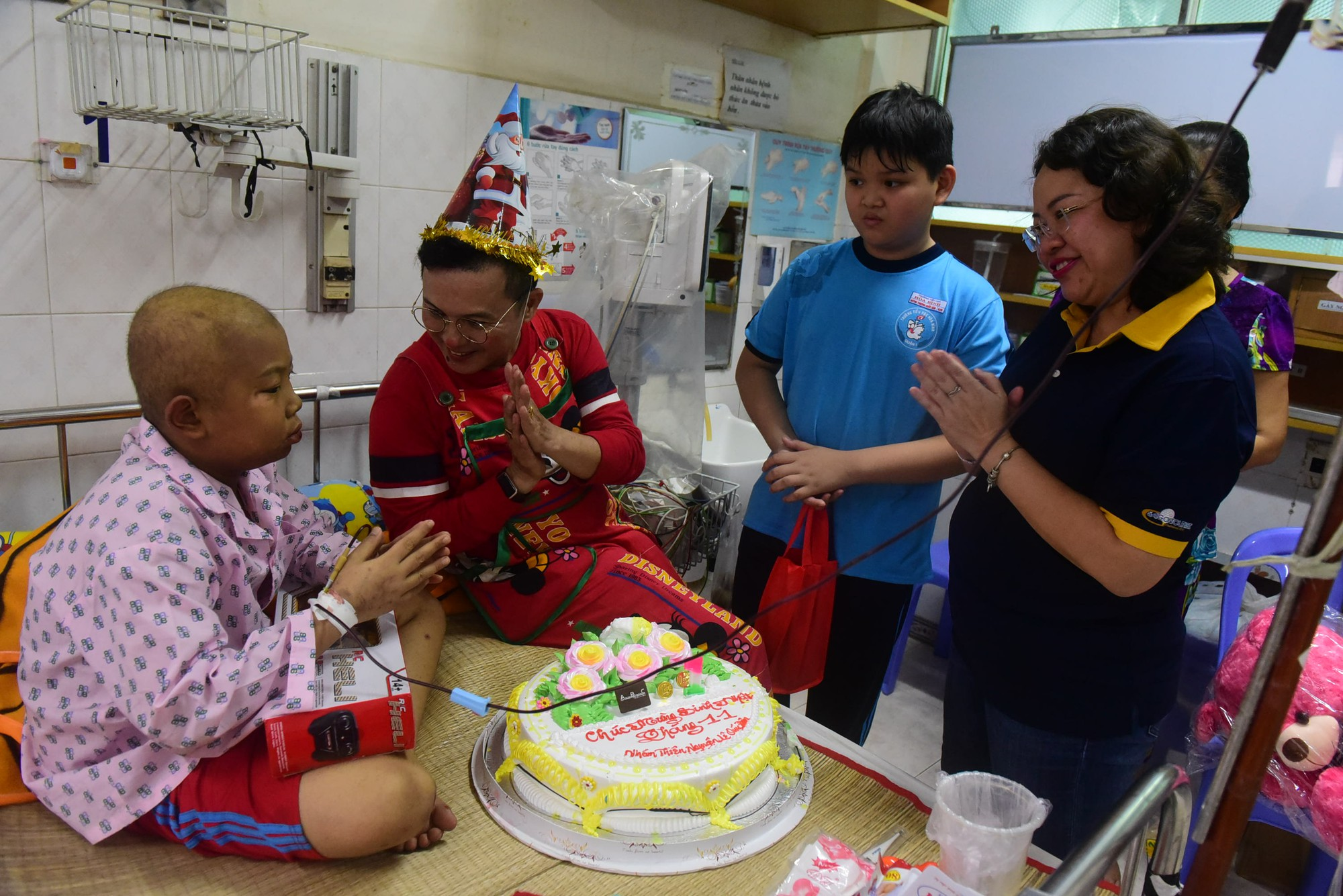 Le Van Hai (red) talks with a child patient at the Ho Chi Minh City Oncology Hospital in Ho Chi Minh City, Vietnam. Photo: Tuoi Tre