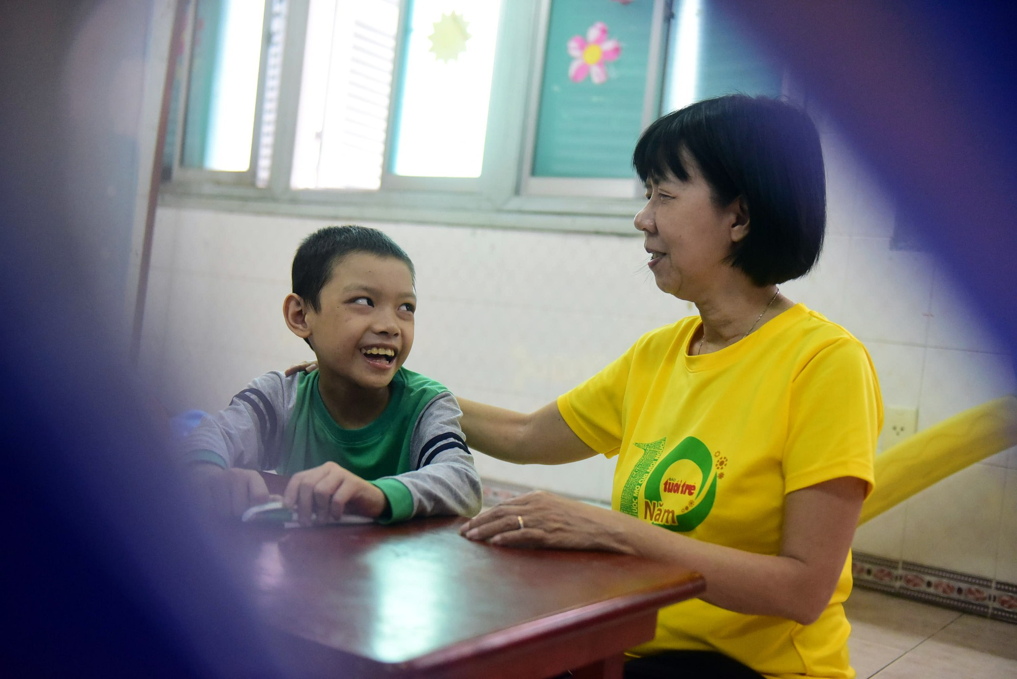 Dinh Thi Kim Phan sits with a child cancer patient at the Ho Chi Minh City Oncology Hospital in Ho Chi Minh City, Vietnam. Photo: Tuoi Tre