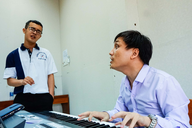 Vu Cong Hao helps students practice their singing skills. Photo: Tuoi Tre