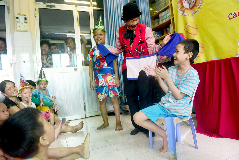 The young boy assists a magician with his tricks at the classroom.