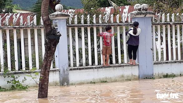 Residents climb along a fence to cross a flooded street in Nha Tranh City, Khanh Hoa Province. Photo: Tuoi Tre