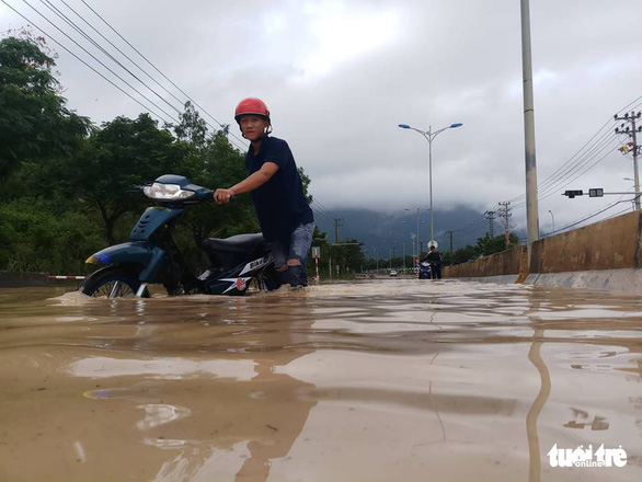 A man pushes in motorbike along inundated Nguyen Tat Thanh Street in Nha Trang. Photo: Tuoi Tre