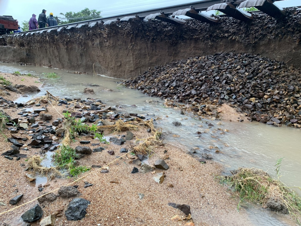Floodwater washes away soil underneath the railway track in Ninh Thuan Province. Photo: Tuoi Tre
