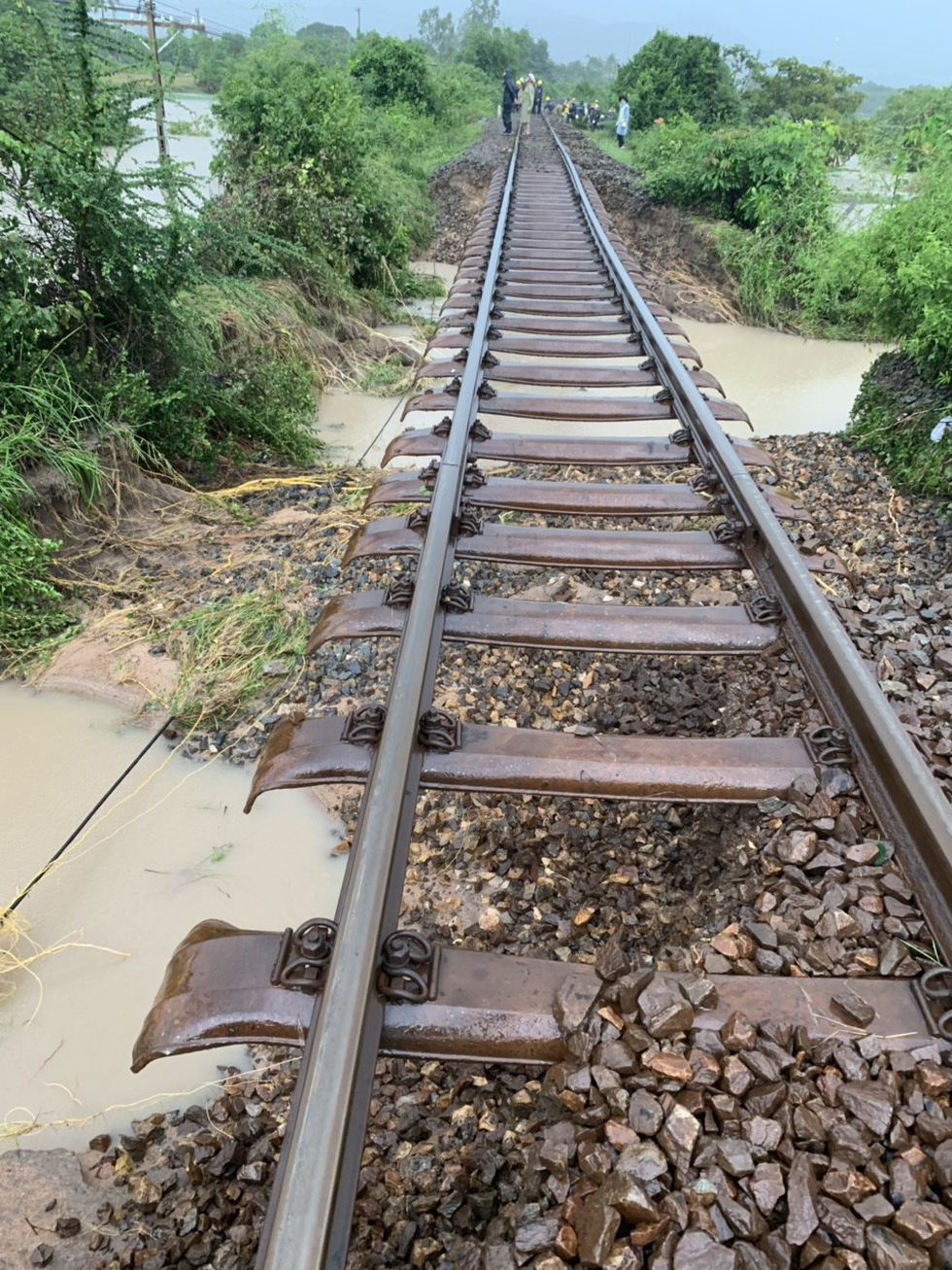 Floodwater washes away soil underneath the railway. Photo: Tuoi Tre